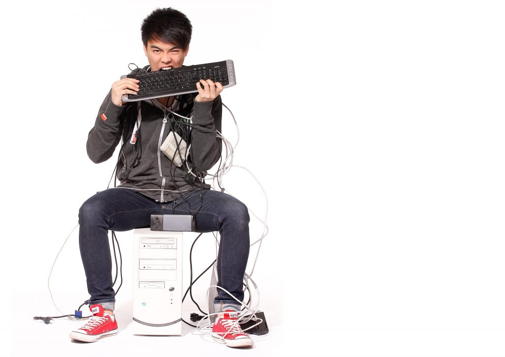 Man looking really stressed, biting his computer